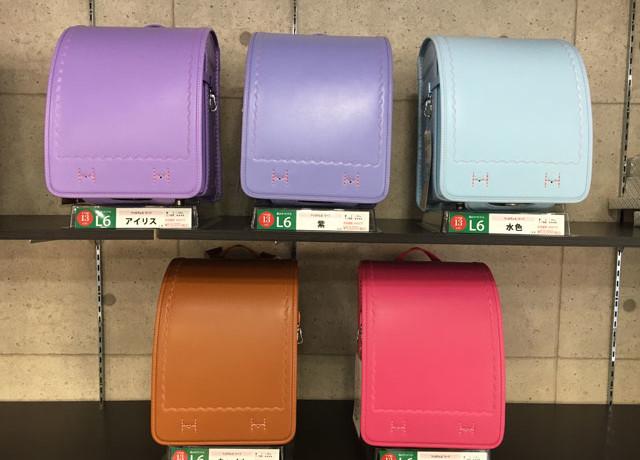 アイリス、紫、水色、キャメル、ピンクのランドセルが棚に並んでいる