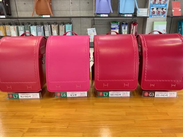 4種類のピンクのランドセルが机に並んでいる
