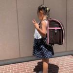 茶色とピンクの縁取りのランドセルを女の子が背負ってポーズを決めている画像