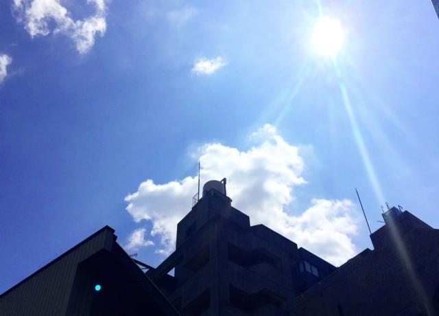 建物の隙間から太陽が見えている空